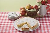 Apple tart with icing sugar, a piece cut