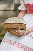 Woman in traditional costume holding coarse rye bread
