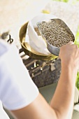 Woman putting cereal grains into paper bag on scales