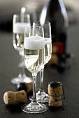 Sparkling wine glasses, corks and bottle of sparkling wine