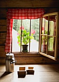 Milchkanne und Holzmodeln vor dem Fenster einer Almhütte