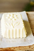 Farmhouse butter shaped in wooden mould on paper