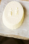 Farmhouse butter shaped in a wooden mould on paper