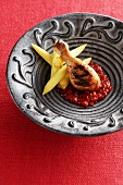 Grilled chicken drumstick with tomato sauce and baby corn cobs