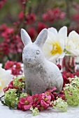 A stone rabbit surrounded by japonica and viburnums