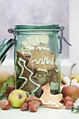 Spekulatius (German Christmas shortcrust biscuits) in a preserving jar surrounded by apples and nuts