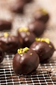 Chocolate coated marzipan pralines with pistachios