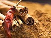 Cinnamon sticks and dried chilli on ground cinnamon