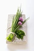 Ein Bund Schnittlauch mit Blüten und Schnittlauchröllchen