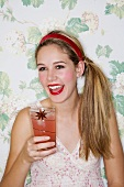 A girl drinking a plum cocktail