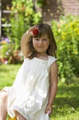 A little girl in a garden holding up a strawberry