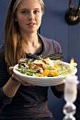 A young woman holding a bread salad with fennel and mandarins