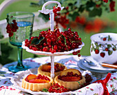 Tiered stand with redcurrants and small cakes