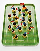 Cheese on cocktail sticks with flags on football pitch tray