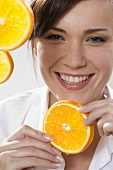 Young woman holding slice of orange