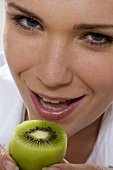 Young woman with kiwi fruit (close-up)