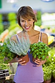 Young woman with pots of herbs in a supermarket