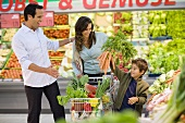 Family buying vegetables in a supermarket