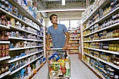 Young man with shopping trolley in a supermarket