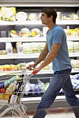 Young man pushing a shopping trolley in a supermarket