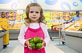 Girl holding limes in her hand in a supermarket