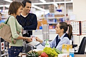 Young couple paying at supermarket checkout