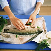 Preparing trout with herbs in foil