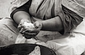 Moroccan woman preparing couscous in traditional manner