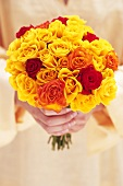 Hands holding bouquet of yellow roses