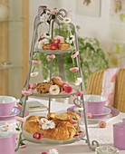 Small cakes, croissants and daisies on tiered stand