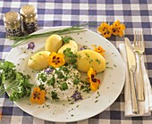 Boiled potatoes with herb quark and edible flowers