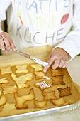 Child brushing biscuits with glacé icing