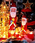 Weihnachtsmänner im Schnee mit Lichterkette