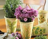 Blühender Schnittlauch und Rosmarin in dekorativen Töpfen