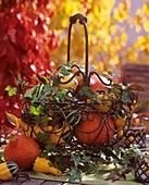 Metal basket decorated for autumn with squashes and ivy