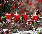 Winterliches Gesteck mit Kerzen im Schnee