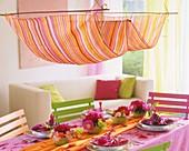 Gedeckter Tisch mit kleinen Frühsommersträußen aus Pfingstrosen, Margeriten, Flockenblumen und Frauenmantel