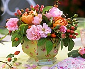 An arrangement of roses and Hypericum berries