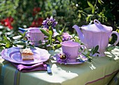 Table laid for coffee in open air with passion flowers