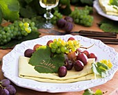 Grapes and vine leaf as place card on napkin
