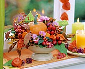 Autumn arrangement in beige metal bowl with pedestal