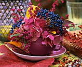 Herbstliches Blumengesteck mit Beeren schmückt einen Tisch