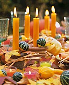 Table decorated for autumn with candles and gourds