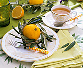 Laid table with lemons and olive branches