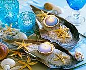 Große Muschelschalen mit Sand, Seesternen und Kerzen