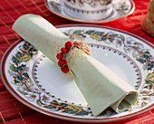 Napkin ring of holly berries and angel's hair