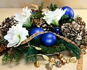 Gesteck aus Amaryllisblüten, Zweigen und Weihnachtskugeln