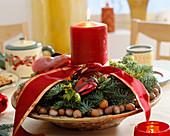 Adventsgesteck mit Kerze und Nüssen