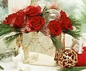Silbervase mit roten Rosen, Seidenkiefer und Engelshaar