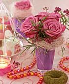 Rosen und Zweige vom Liebesperlenstrauch und Perlenkette
